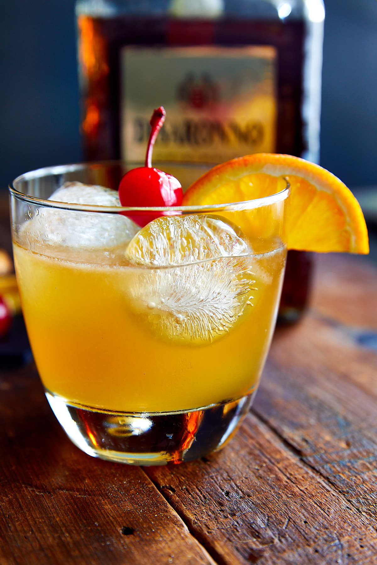Amaretto sour drink in a glass with ice, garnished with a slice of orange and a maraschino cherry.