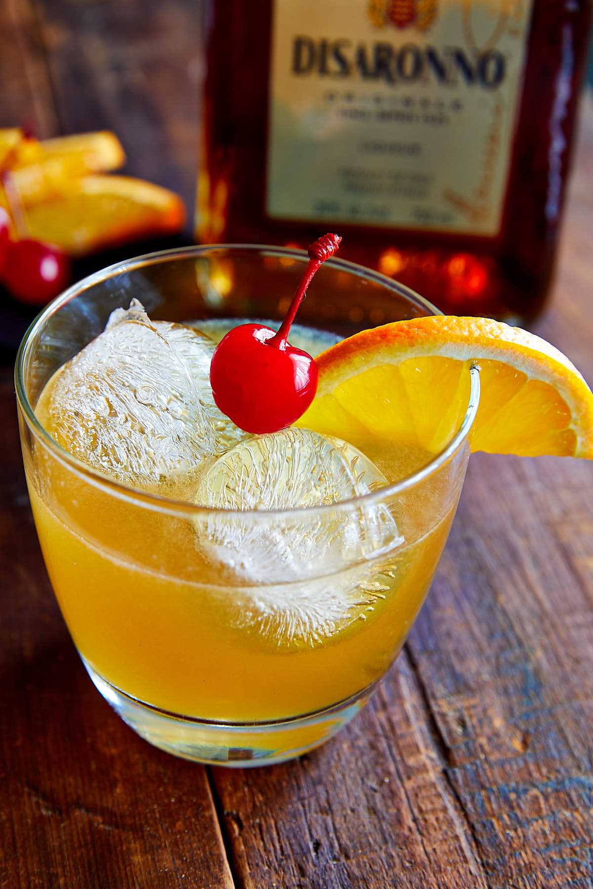 Close up of amaretto sour drink in a glass with ice, orange slice and a maraschino cherry.