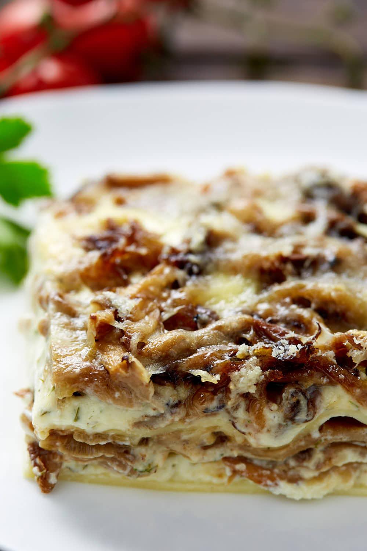 A slice of mushroom lasagna on a plate.