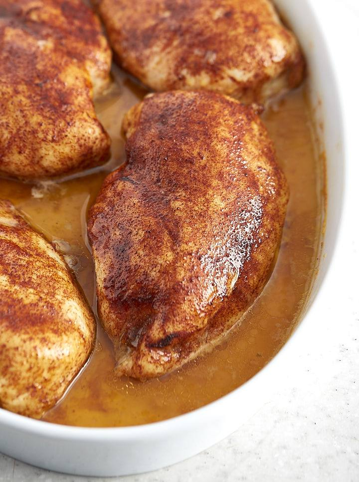 Close up of a large slow baked chicken breast, moist and juicy, inside a baking dish with pan juices.