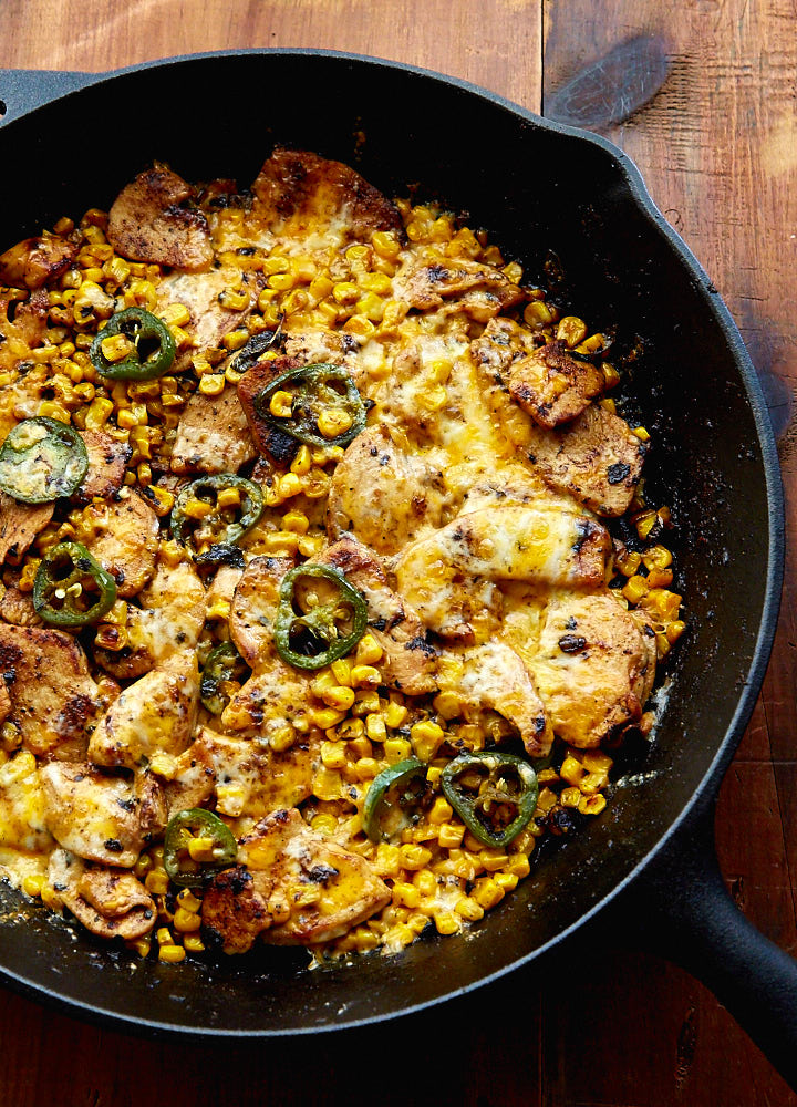 Mexican Chicken with Corn, Chilies and Cheese in a cast iron pan.