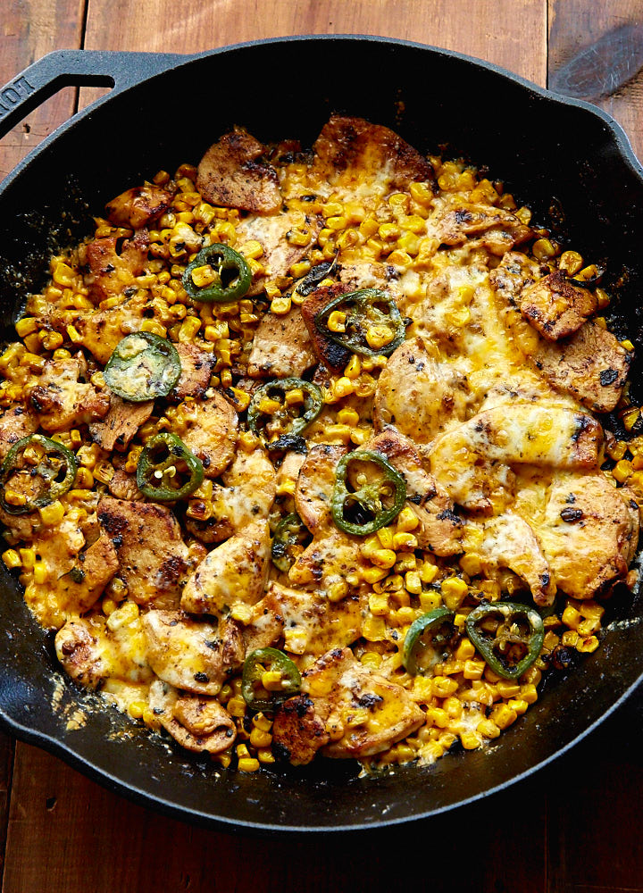Close up of Mexican Chicken with Corn, Chilies and Cheese in a black pan.