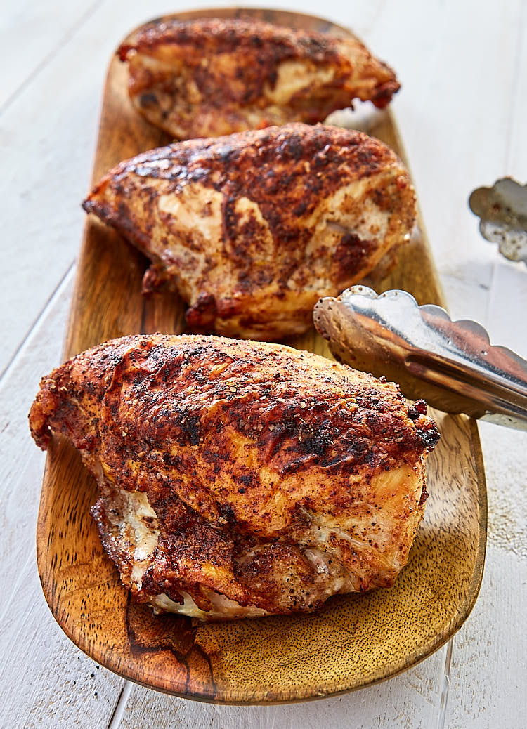 Crispy pan fried, baked chicken breasts on a wooden tray.