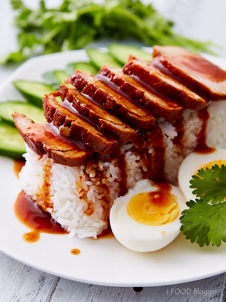 Thai BBQ pork on rice with boiled eggs and cucumbers on a white plate, with sauce poured over.