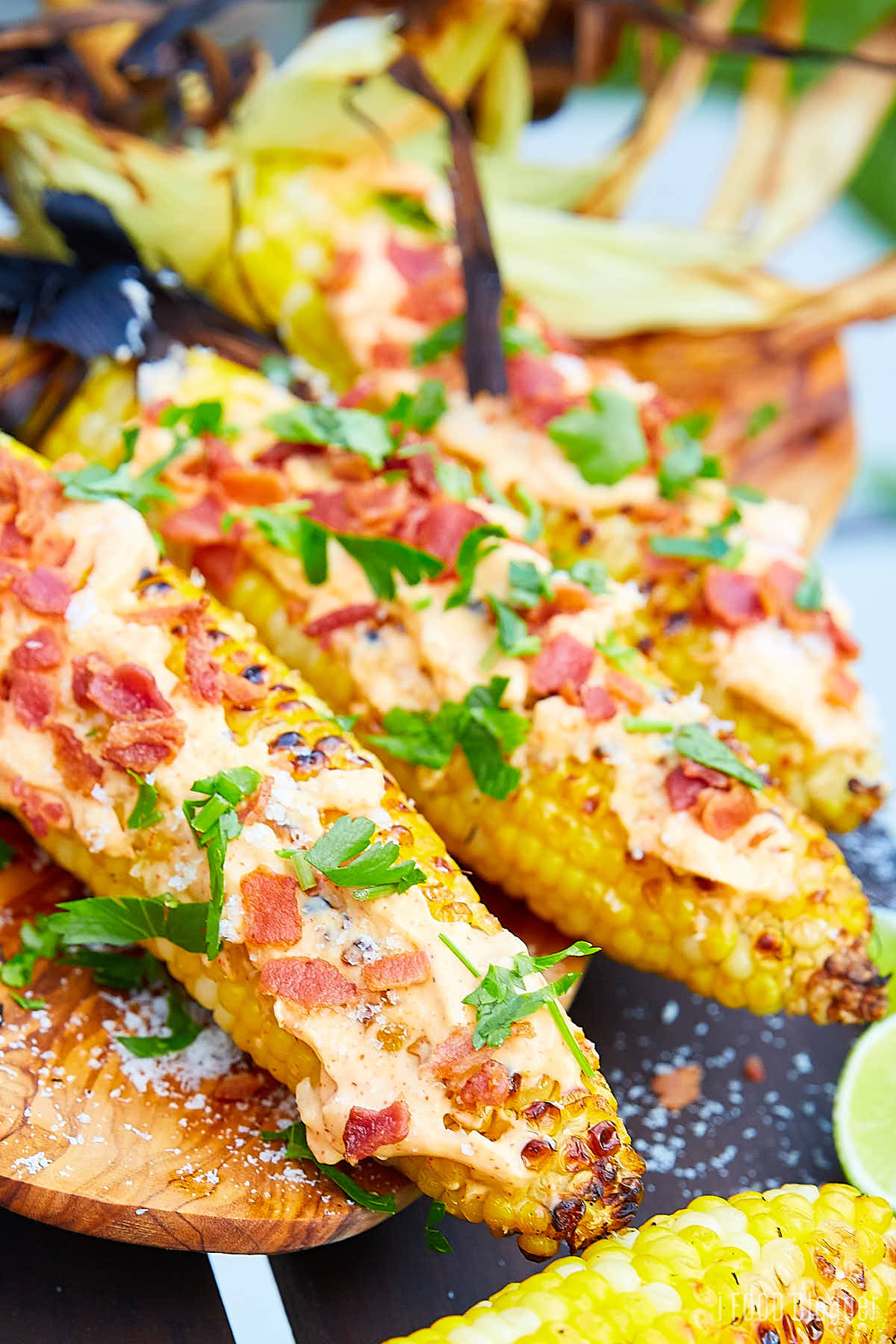Grilled corn on the cob, smothered with mayo and topped with bacon and parsley.