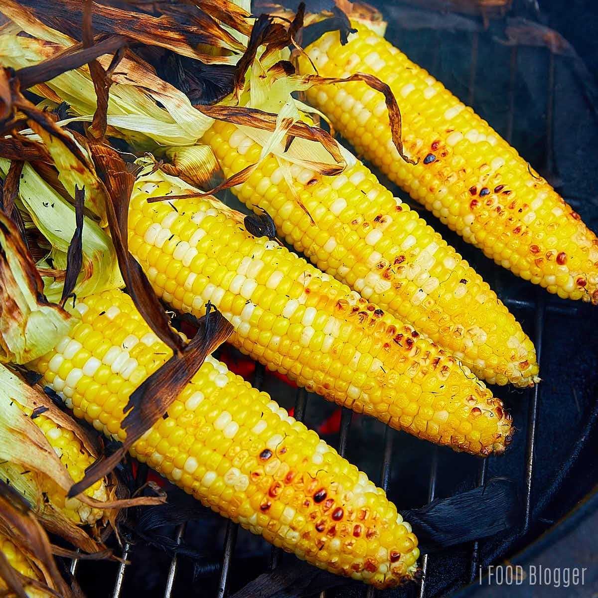 Corn without husks on a charcoal grill.