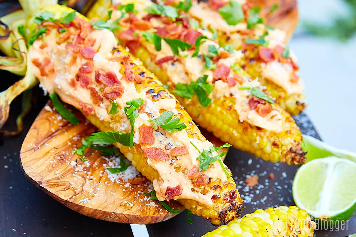 Close up of grilled corn on the cob slathered with mayo and topped with bacon and Parmesan cheese.