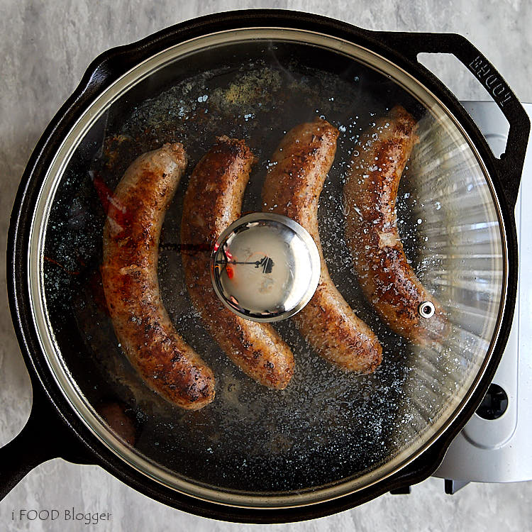 Brats cooking in a pan closed with a lid.