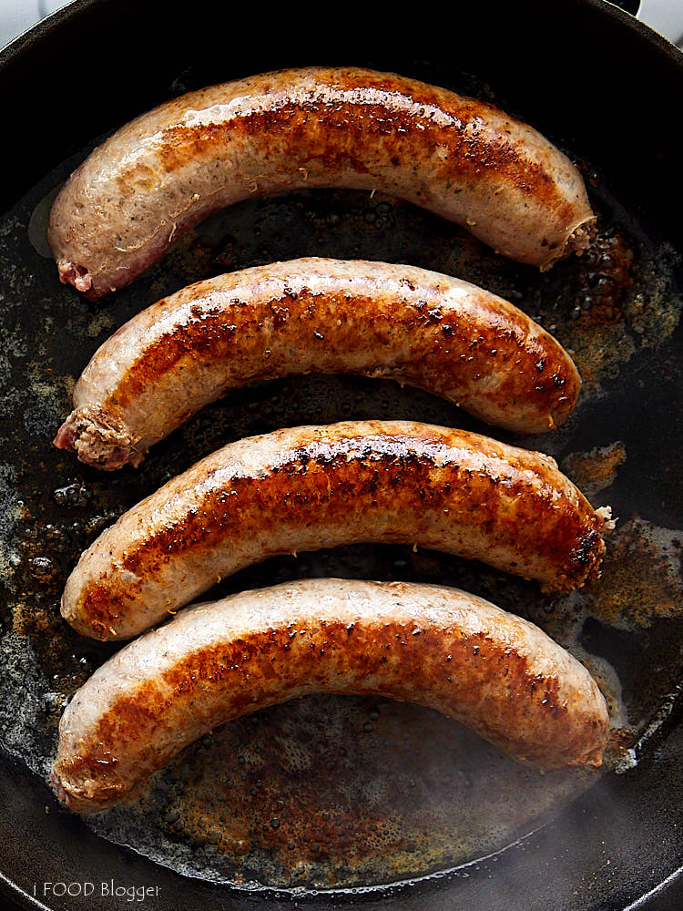 Top down view of four brats in a cast iron pan.