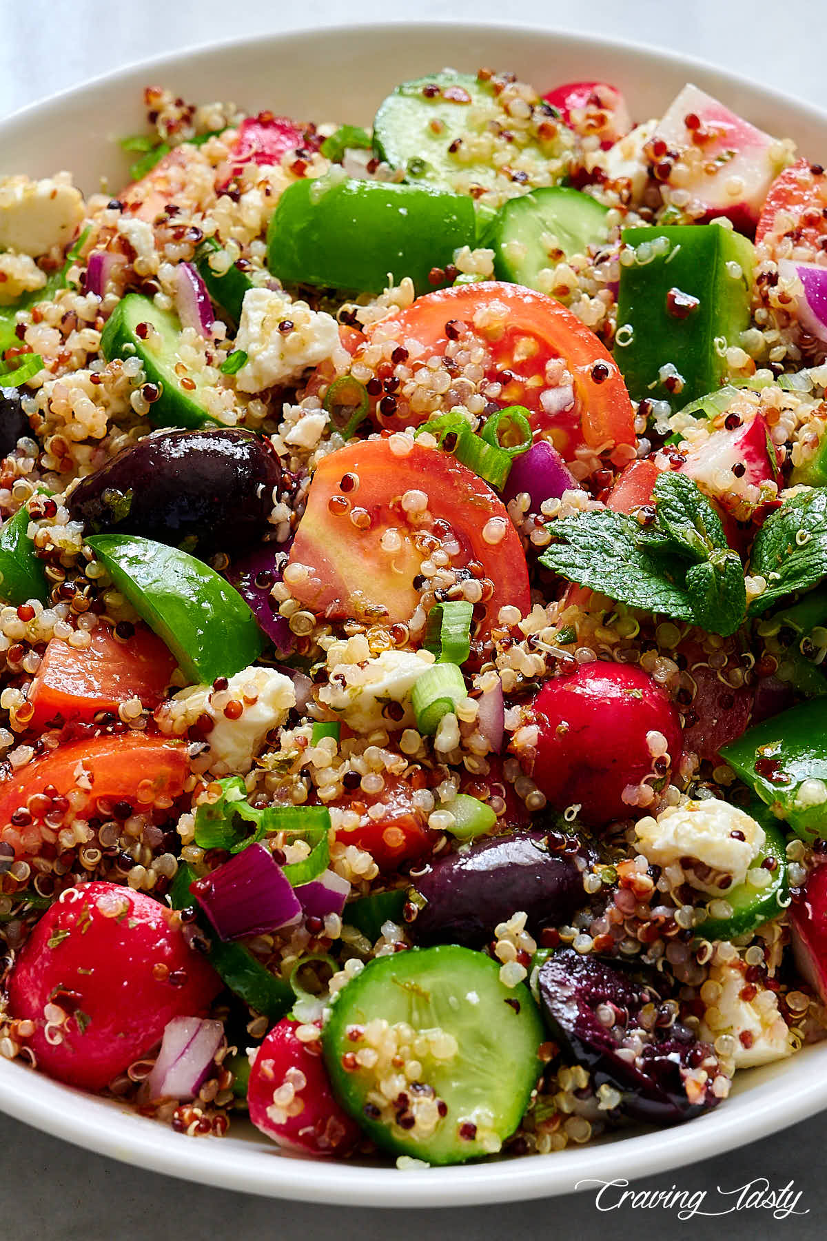 Close up of zesty quinoa salad in a white bowl.