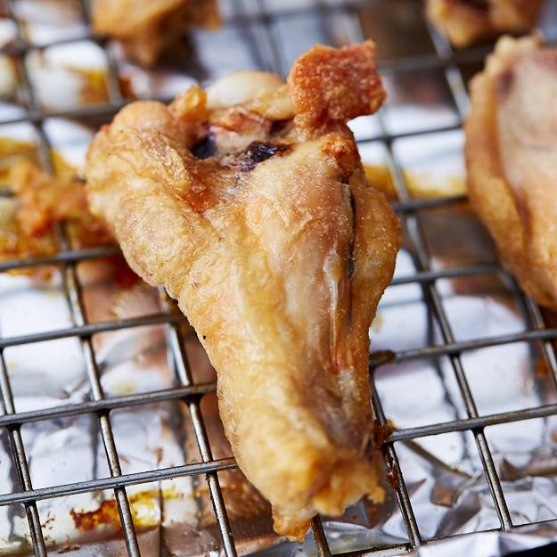 Close up of a crispy chicken wing on a cooling rack.