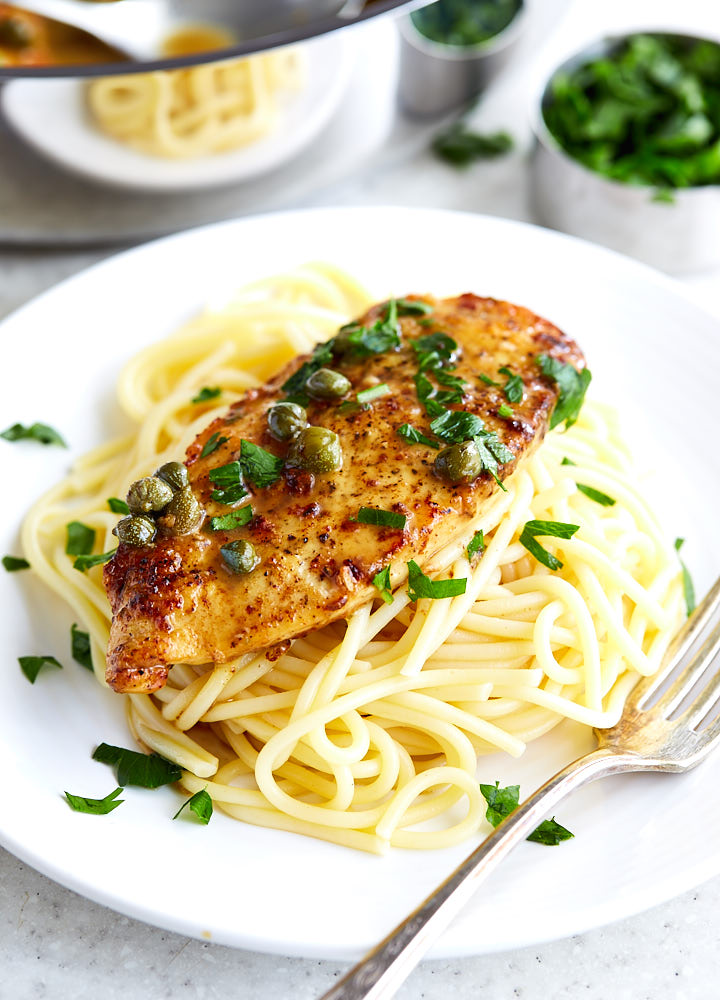 Chicken piccata over a bed of pasta on a white plate, topped with capers and chopped parsley.