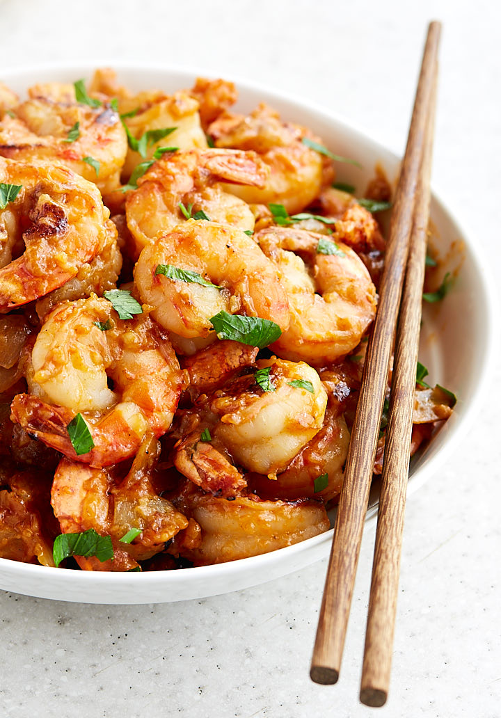 Hunan shrimp in a white bowl with chopsticks on the side.