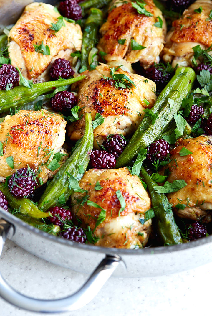 Chicken thighs with okra and blueberries in a pan.