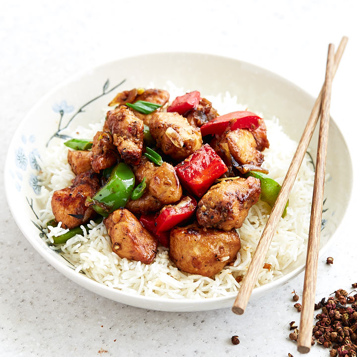 Szechuan chicken in a bowl with peppers over rice.