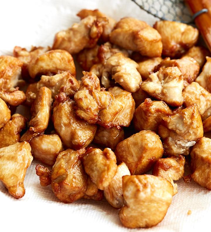 Pieces o fSzechuan chicken on paper towels.
