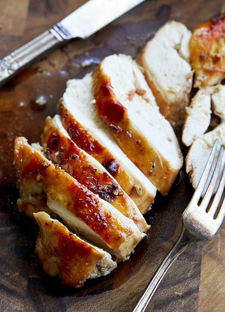 Sliced Asian chicken breast on a brown cutting board with a fork an knife on the side.