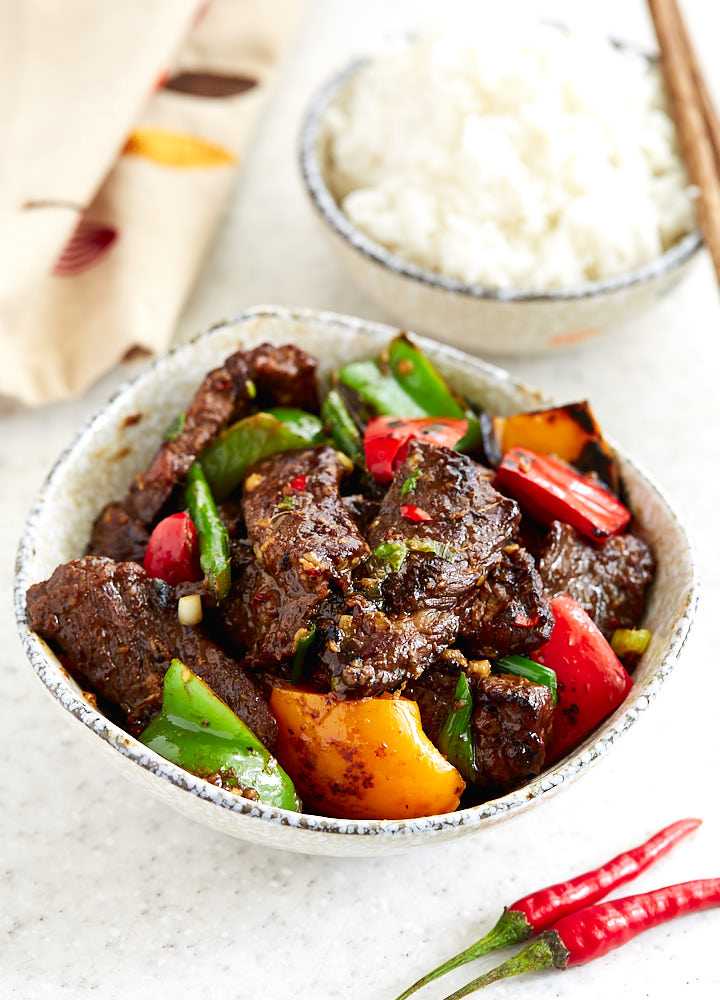 Hunan beef with peppers and asparagus in a bowl, next to a bowl with white rice