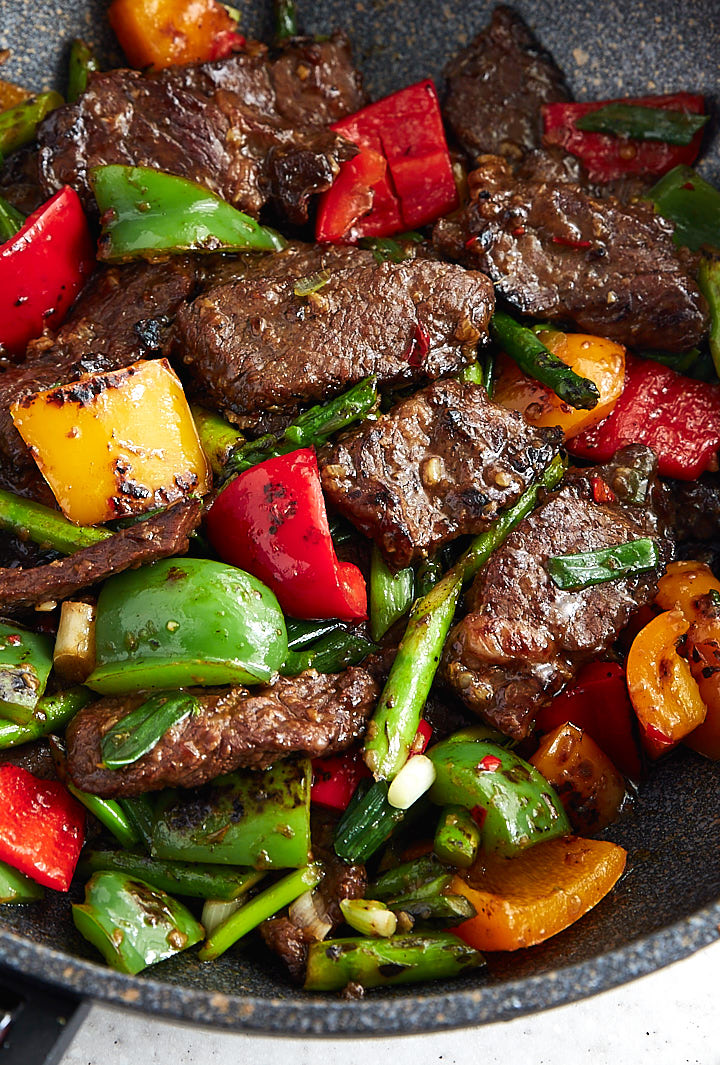 Hunana beef, well-browned, with vegetables in a wok.
