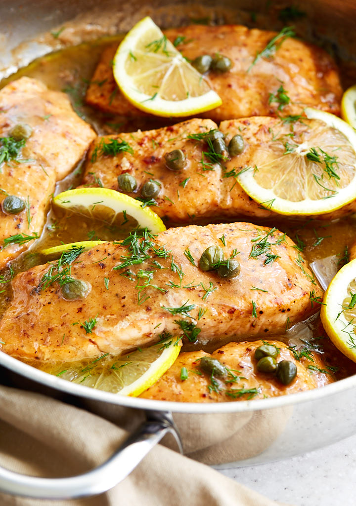 Salmon pieces covered in sauce with lemon slices in a pan.