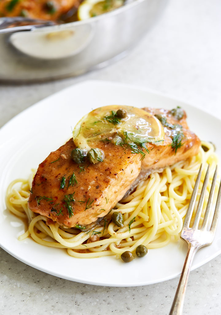 Salmon piccata on a bed of pasta.