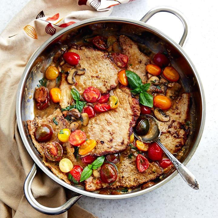 Veal scallopini in a saute pan.