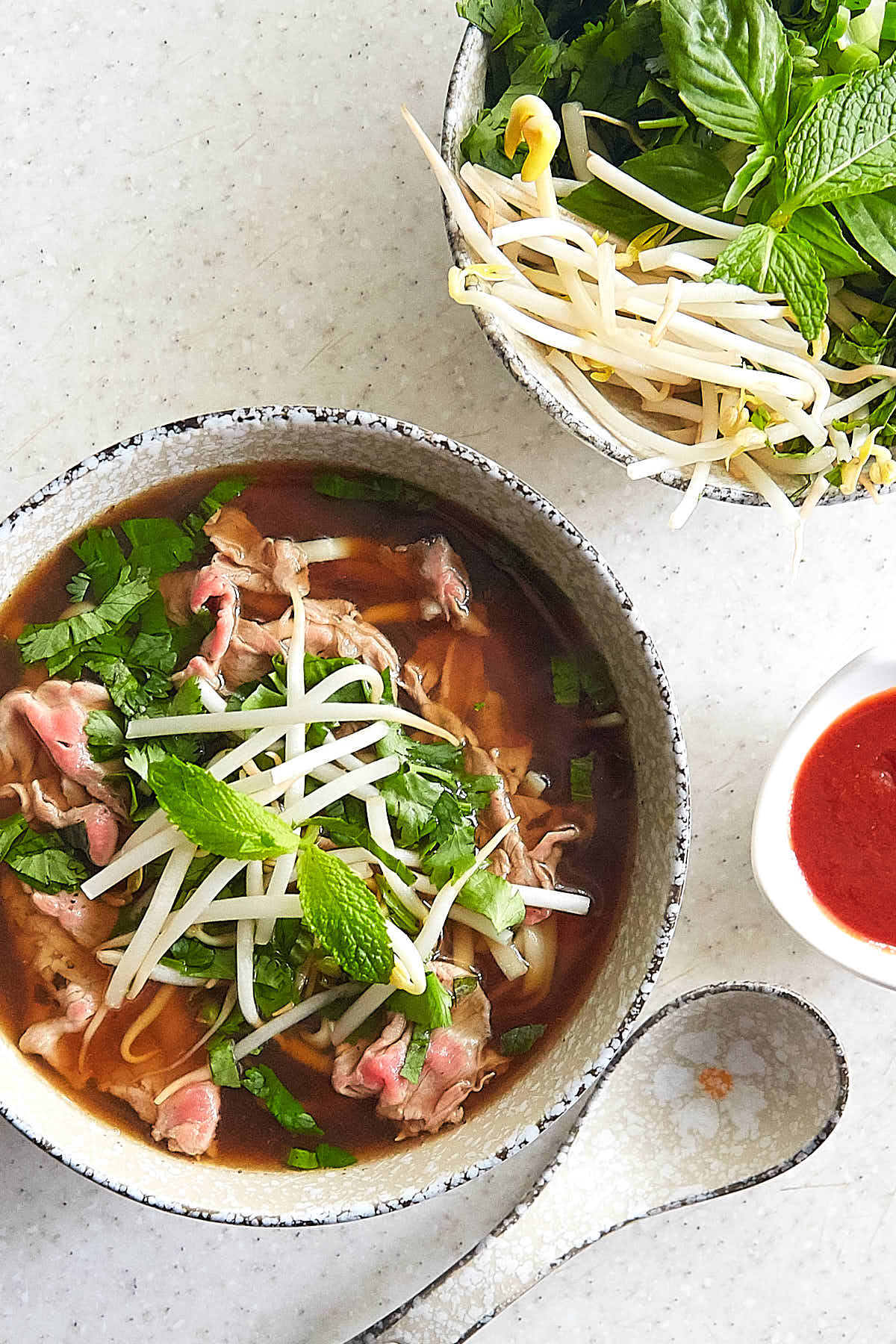 Top down view of Vietnamese pho soup on a bowl garnished with bean sprouts, mint and parsley.