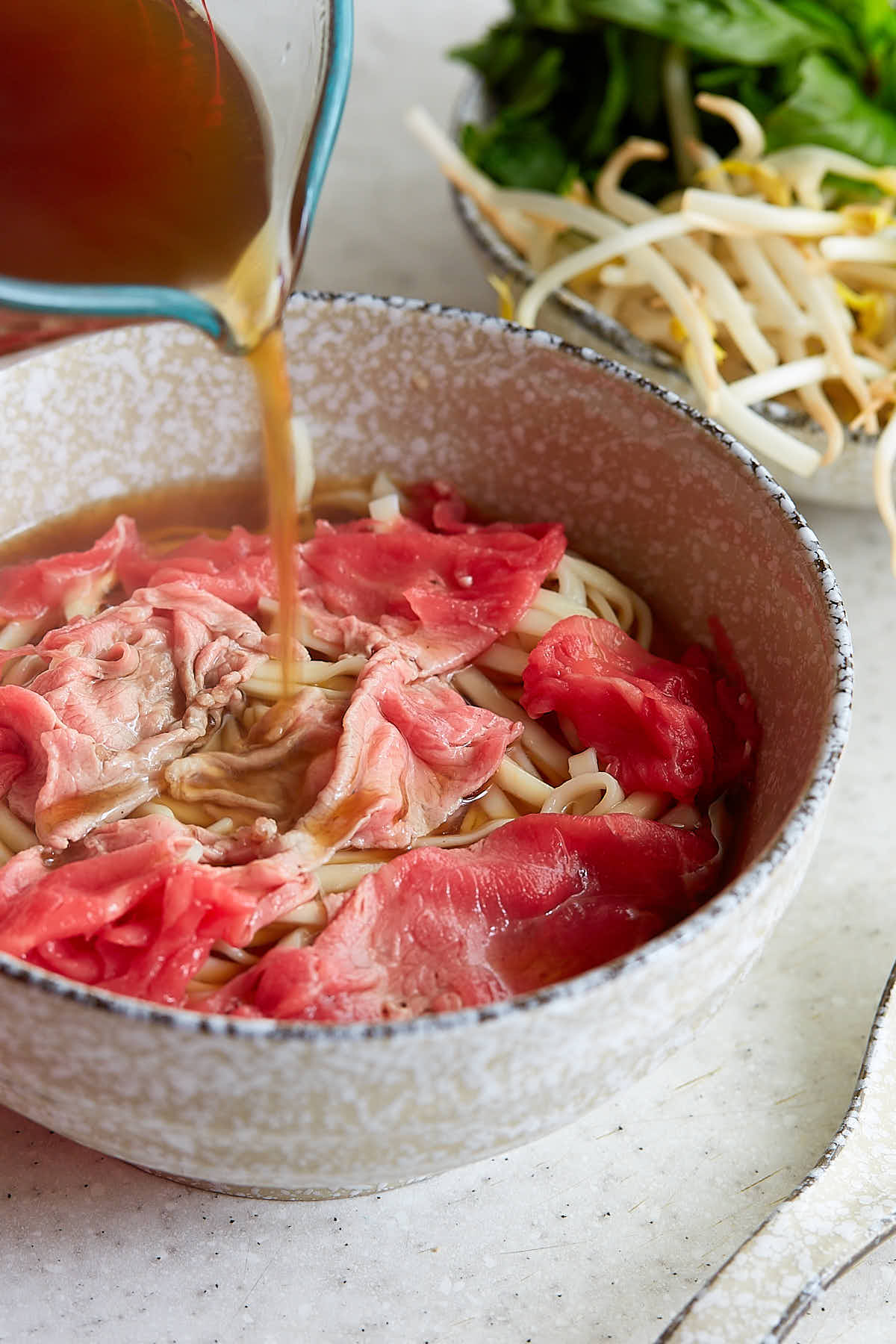 Pouring hot beef broth over raw beef slices in a bowl.