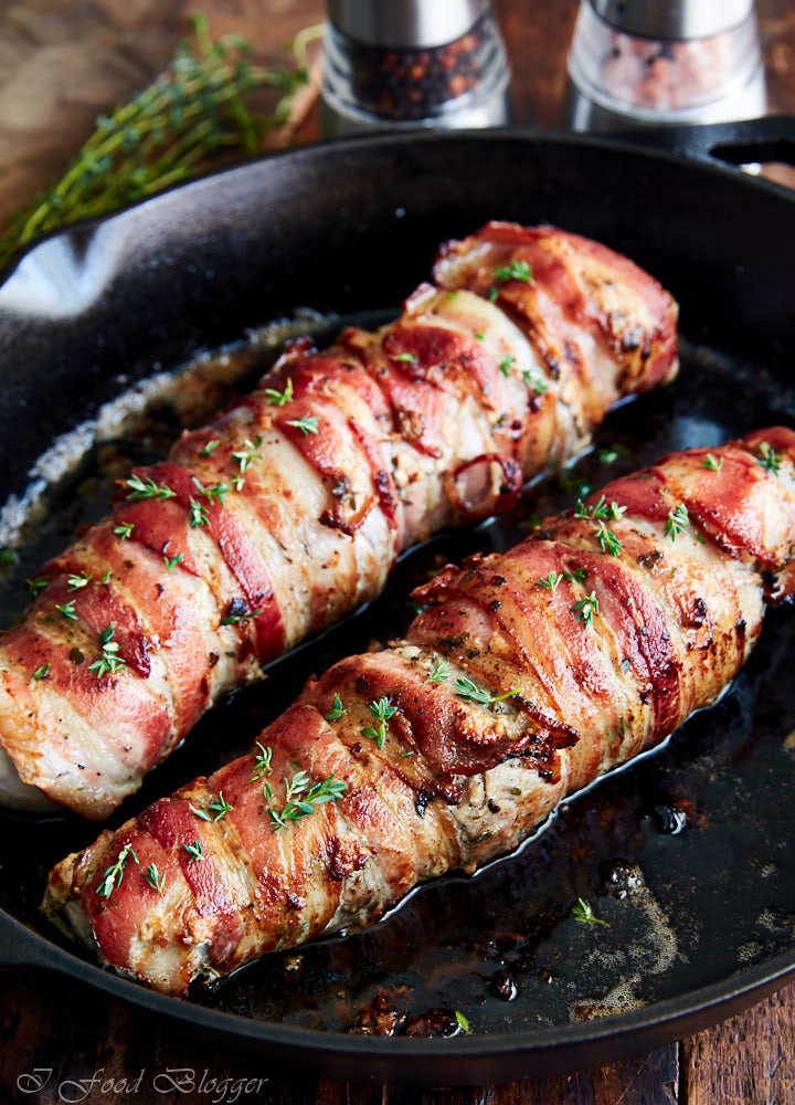 Close up of crispy bacon-wrapped pork tenderloins sprinkled with chopped greens.