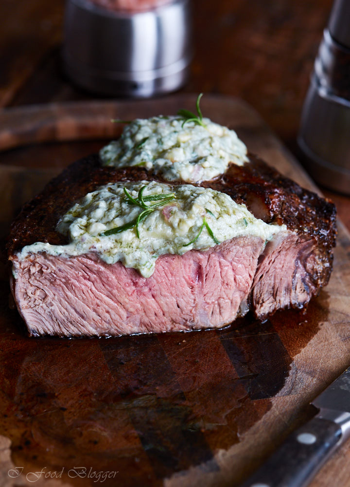 Pan-seared ribeye steak, finished in the oven for perfect doneness, then topped with blue cheese and shallot compound butter and fresh rosemary.