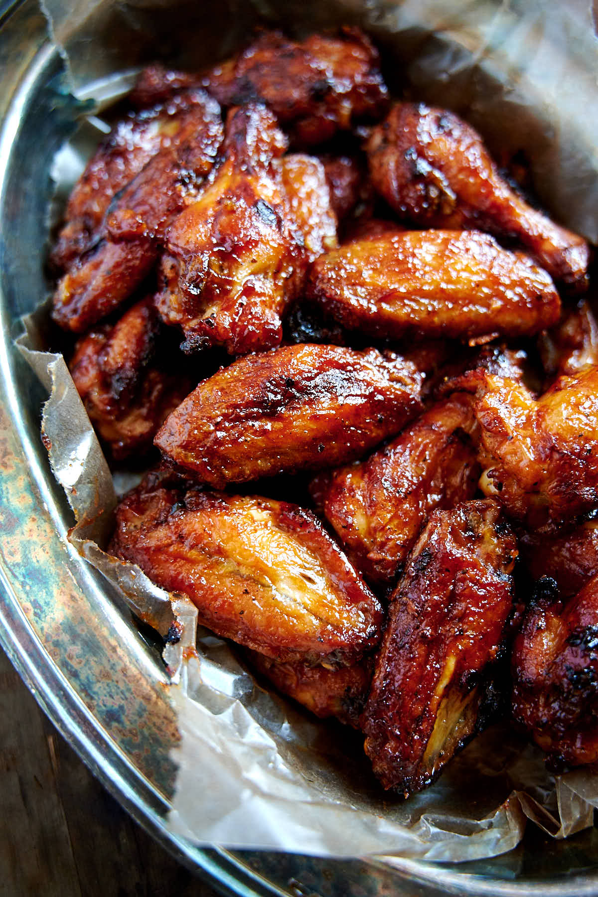 Bright red, crispy BBQ chicken wings in a serving basket.