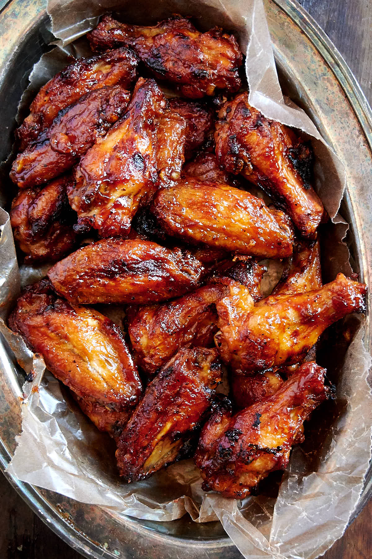 Baked BBQ Chicken Wings in a serving basket lined with wax paper.