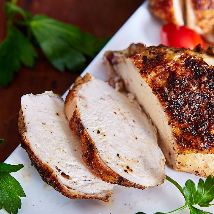 Crispy-skinned, tender and juicy oven roasted bone-in chicken breast sliced on a white platter.