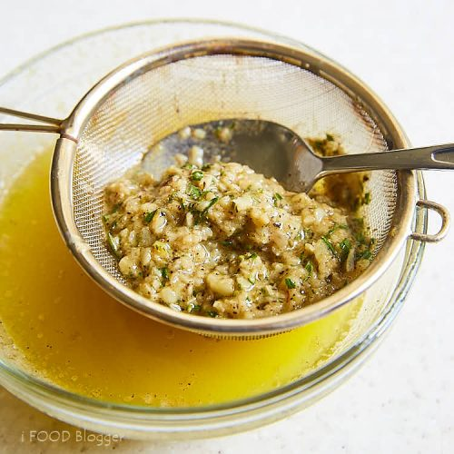 Roasted turkey breast - straining butter after infusing with herbs and garlic. | ifoodblogger.com