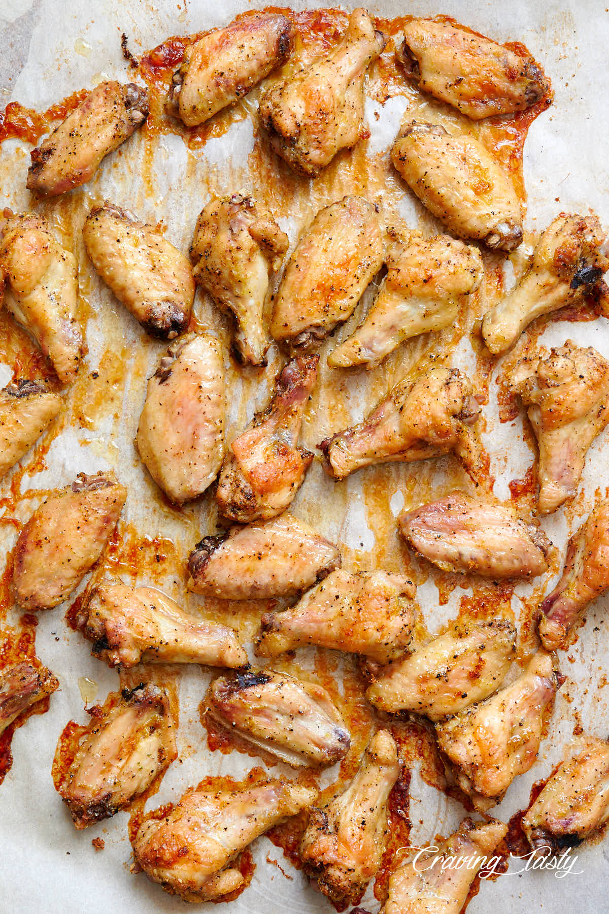 Lemon pepper chicken wings, fully baked, well-browned and crispy, on a baking tray lined with parchment paper.