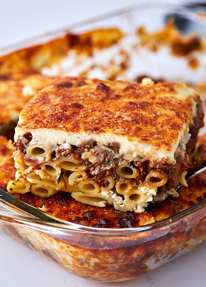 A slice of Greek lasagna on top of lasagna in a baking dish.
