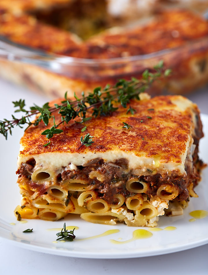 A slice of Greek Lasagna on a white plate drizzled with olive oil and garnished with a twig of Thyme.