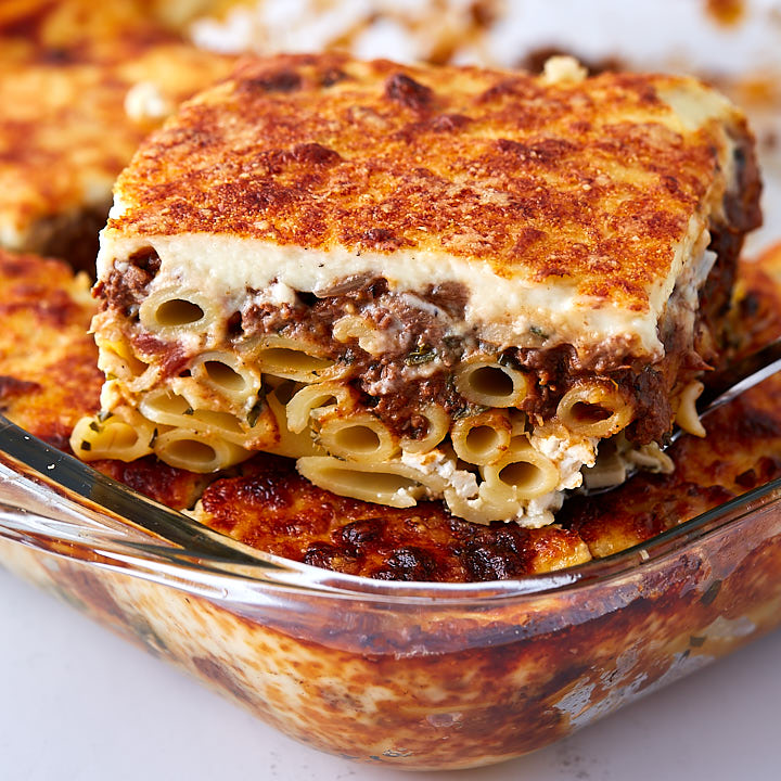 A close up of Greek lasagna slice showing ziti noodles, bechamel sauce and meat filling.