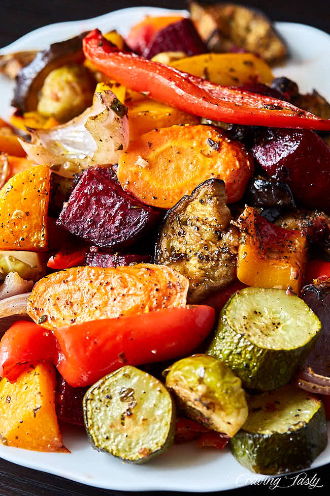 Close up of a variety of roasted vegetables on a white serving platter.