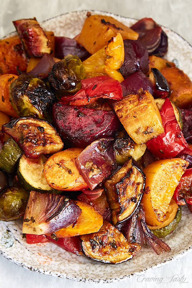 Close up of roasted beets, eggplant, onions, butternut squash and other vegetables covered in delicious dressing and fresh chopped herbs.