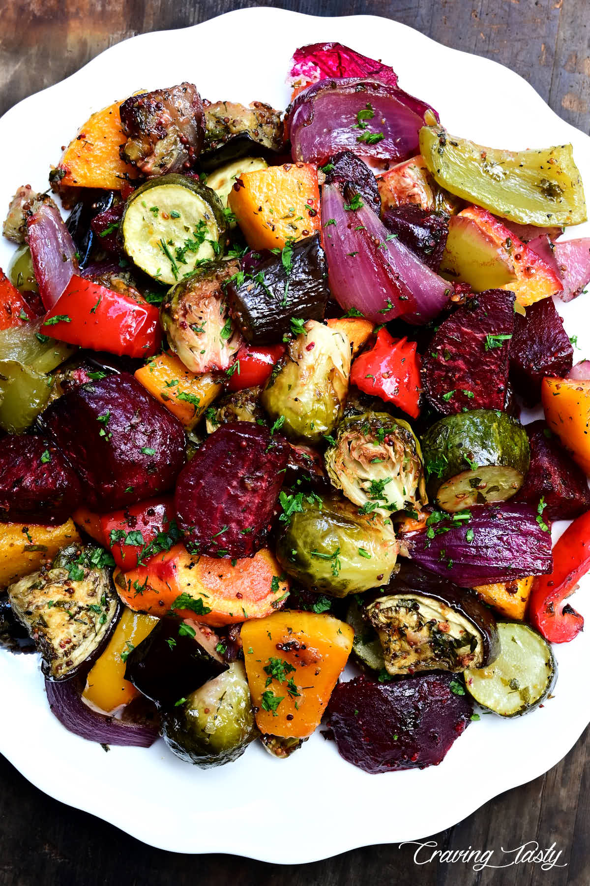 Assorted roasted vegetables on a white plate sprinkled with chopped herbs.