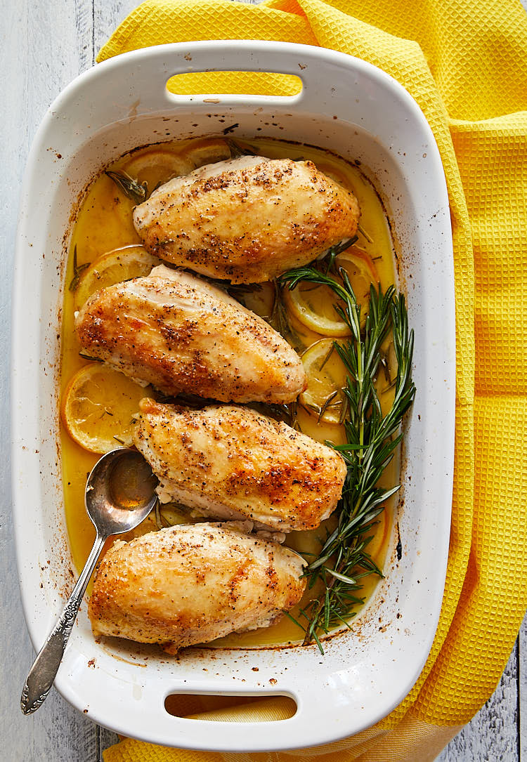 Rosemary and Lemon Chicken in a large white baking dish with lemon slices and rosemary twigs.