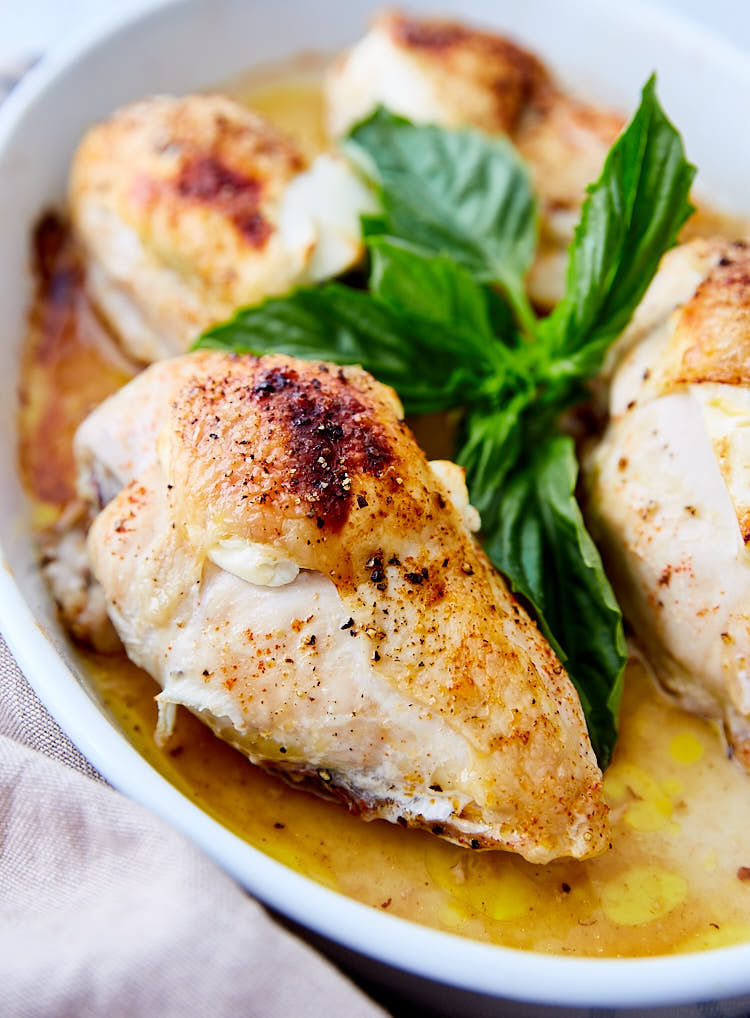 Crispy chicken breasts with basil in a baking pan.