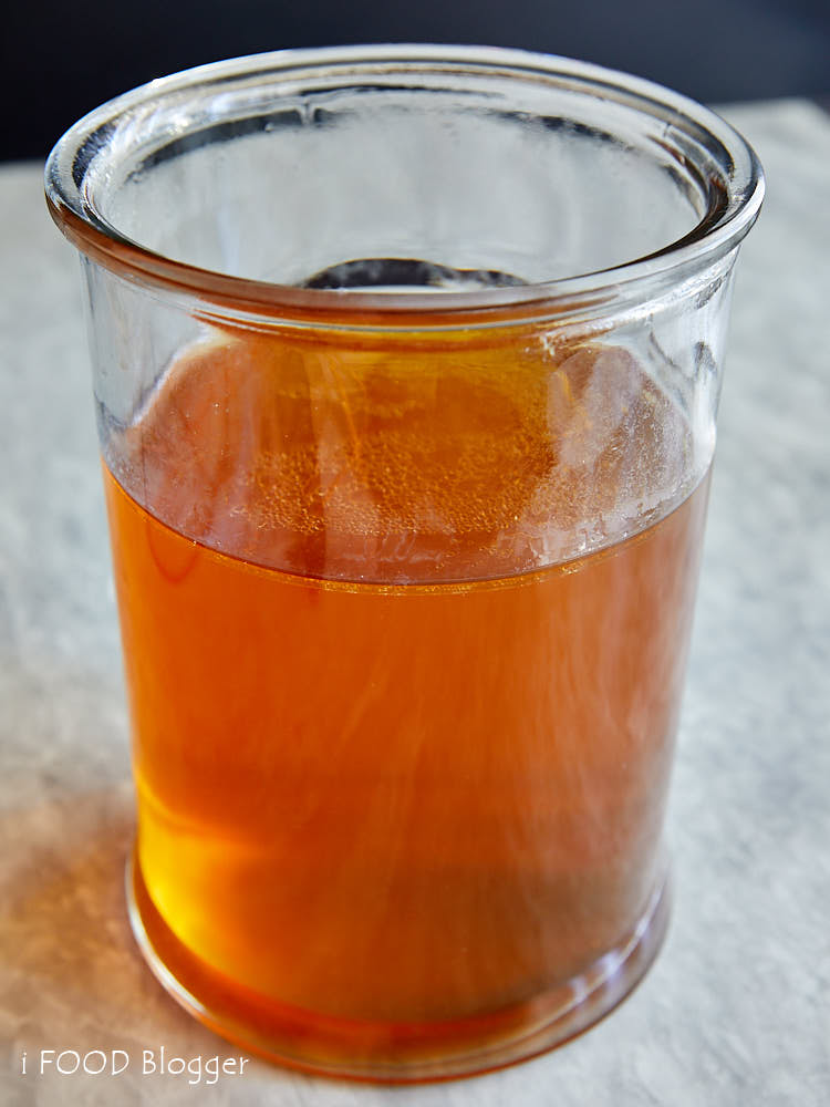 Clarified Beef Consomme in a tall wide glass jar.