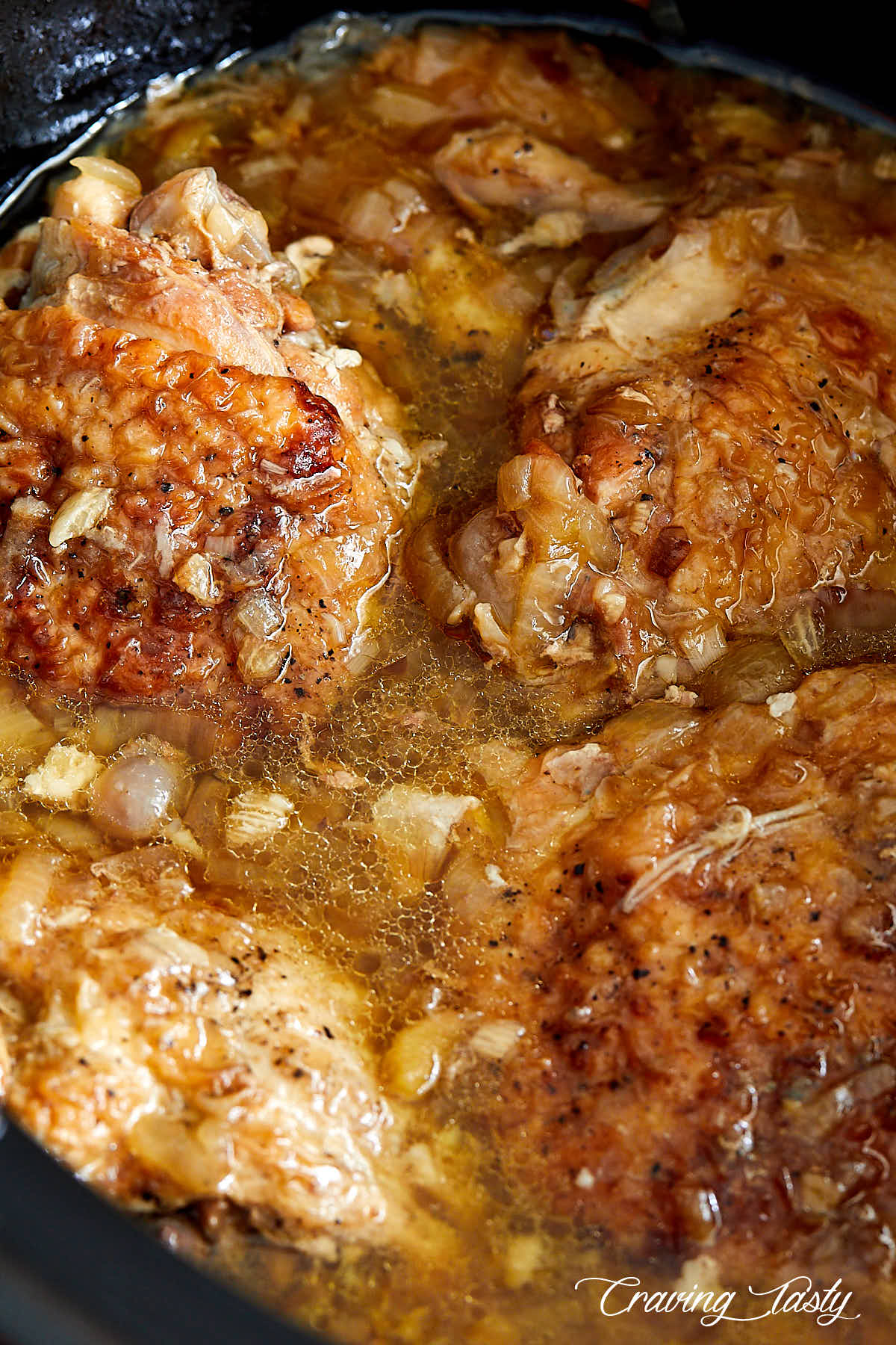 Chicken thighs inside a slow cooker, covered in juices.
