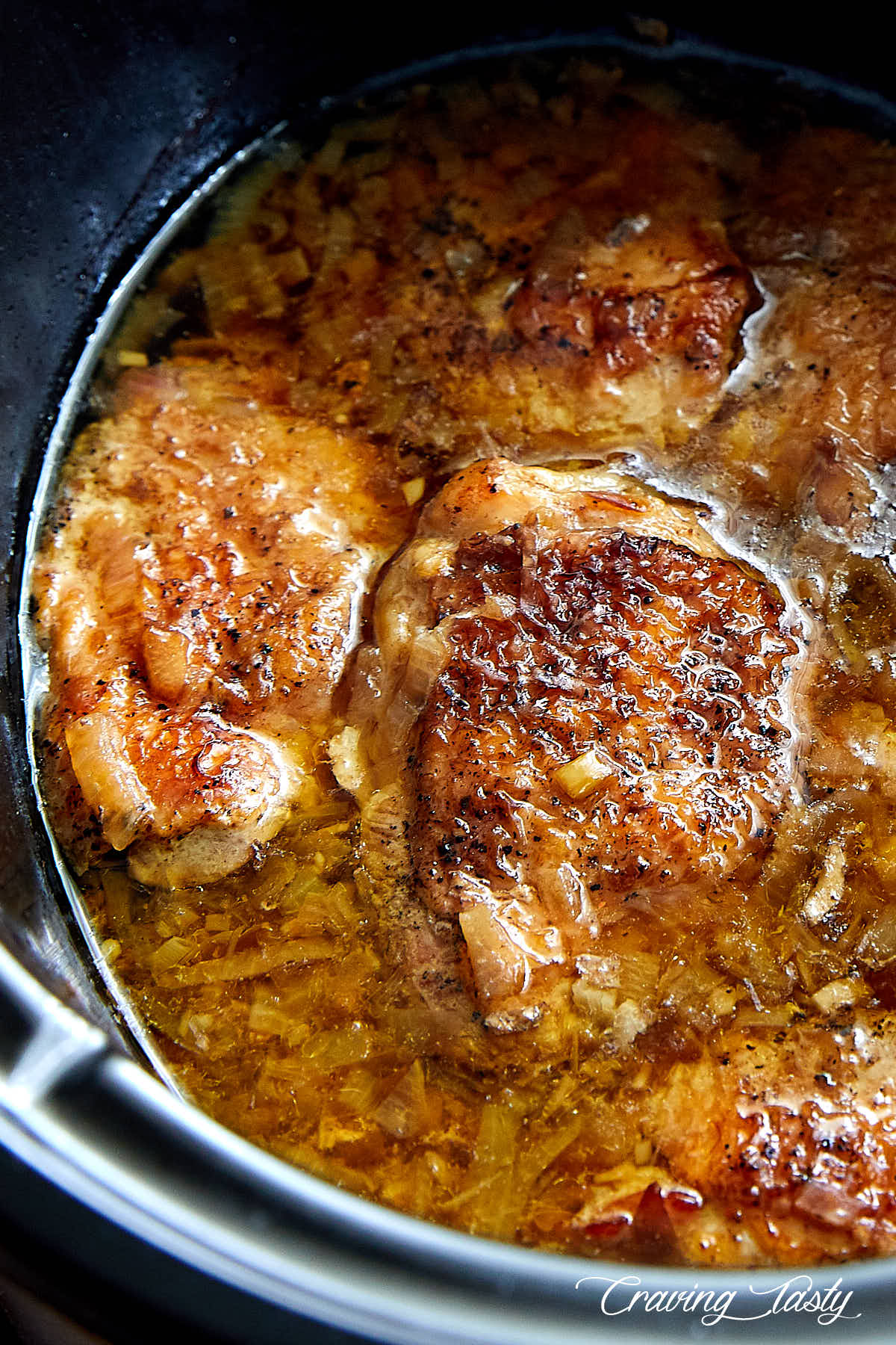 Close up of golden brown chicken in a slow cooker in juices.