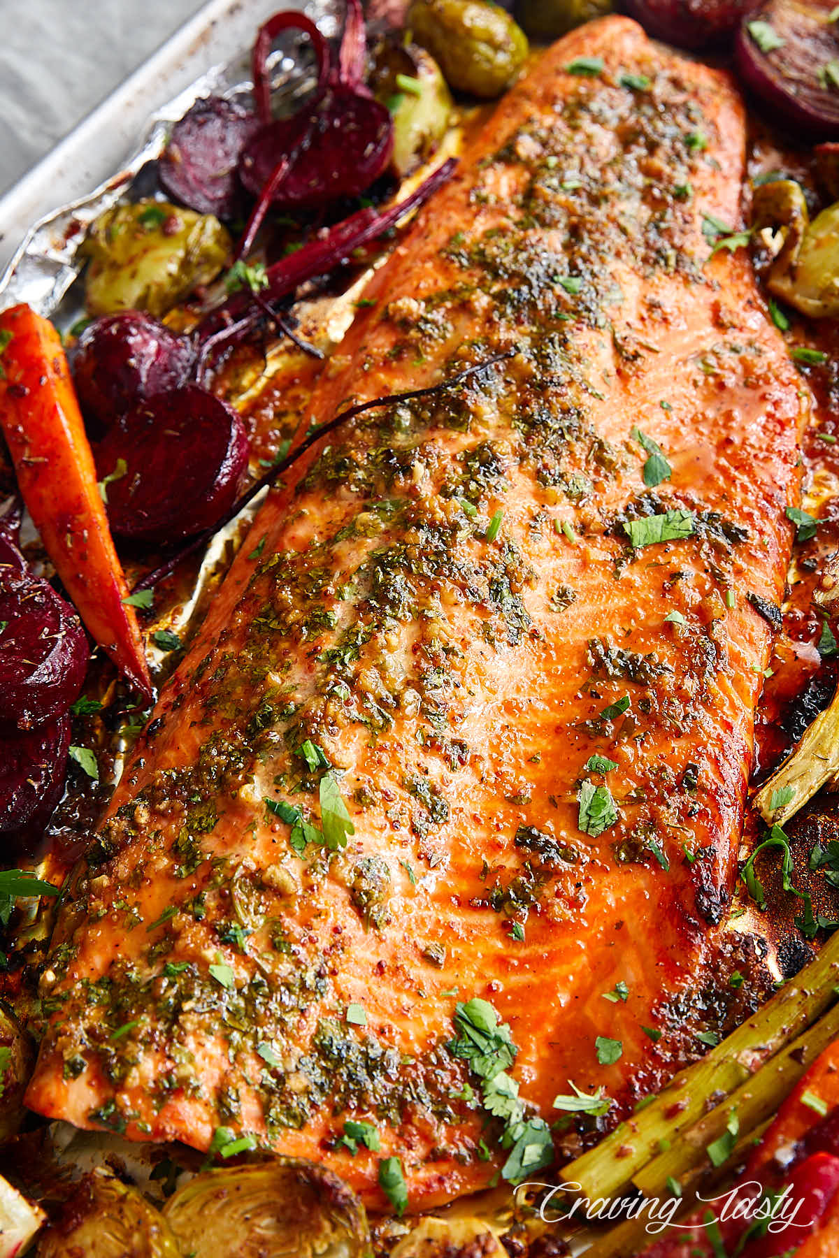 Steelhead trout filet on a piece of foil surrounded by roasted vegetables.