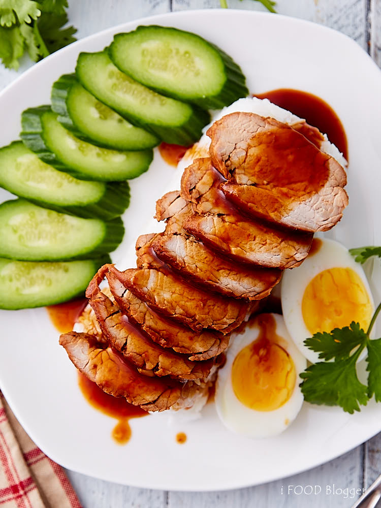 Top down view of Thai BBQ pork on rice with boiled eggs and cucumbers on a white plate, with sauce poured over.