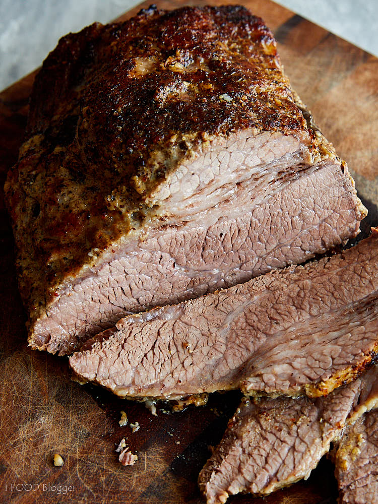 Juicy, well-browned oven-baked brisket sliced on a cutting board.
