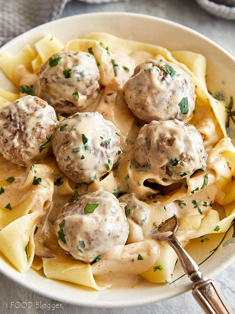 A close up of a white bowl full of Swedish meatballs with cream of mushroom sauce over pasta.